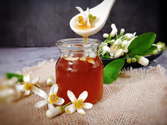 Mật ong ngâm hoa bưởi có tác dụng bị viêm họng, tiêu đờm hoặc pha loãng với nước ấm, pha trà đều rất tốt. Ảnh: Bùi Thủy.
