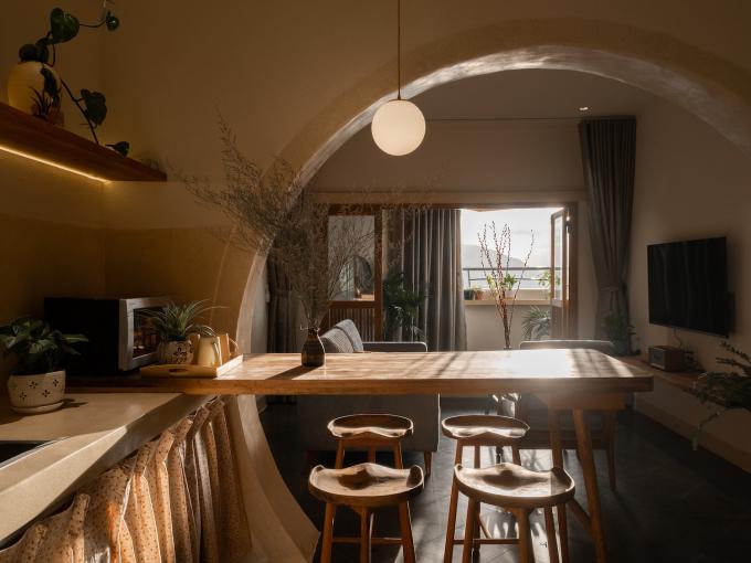 Để tiết kiệm không gian, bàn ăn kết hợp với bàn bar. Từ vị trí này, người ở cũng có thể nhìn ra ban công.