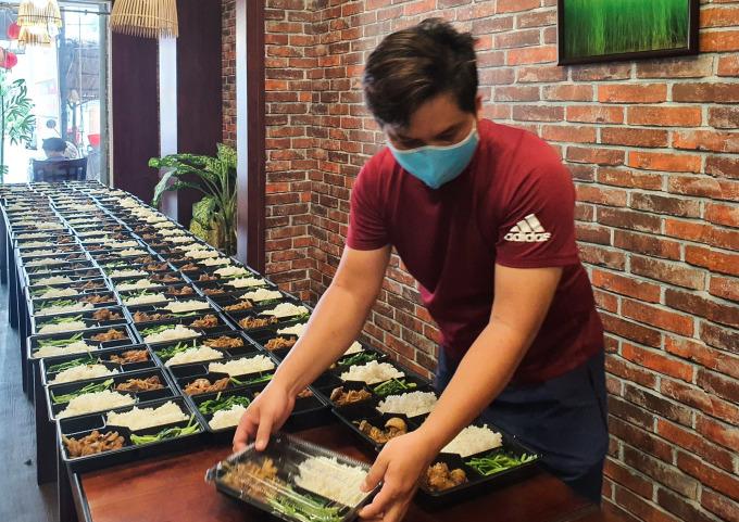 Anh Hiền đang vào hộp các món ăn trưa ngày 31/5. Ảnh: Minh Hiền.