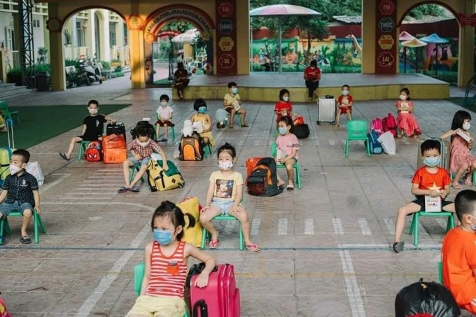 Các bé ngồi chờ gia đình đến đón sau khi kết thúc thời hạn cách ly. Ảnh: Trường mầm non Lê Lợi.