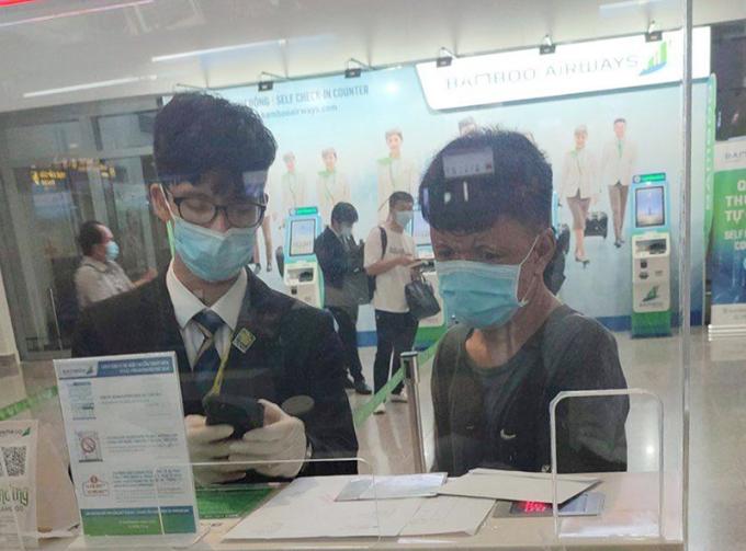 Anh Nguyễn Quốc Phương (bên phải) làm thủ tục check-in chuyến bay cuối ngày về quê, chiều tối 31/5. Ảnh: Thu Thảo.