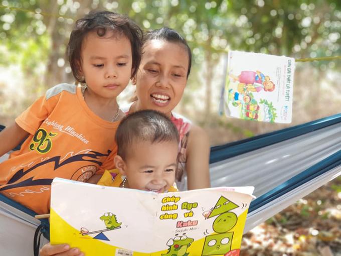 Trên hành trình ngao du của gia đình, cứ dừng chân cắm trại là Thộn và Nấm đều lôi sách truyện ra đọc theo sở thích. Chị Thúy chỉ là người hướng dẫn. Ảnh: Nhân vật cung cấp.