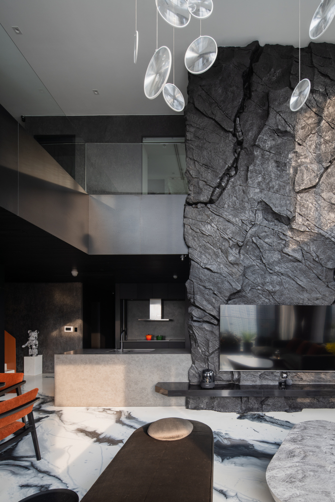 Vách đá đen cao sáu mét và sàn đổ epoxy với hoa văn độc nhất vô nhị tạo nên sự khác biệt cho căn hộ.