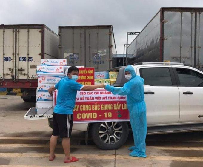 Anh Linh (trái) nhận hàng từ các đoàn thiện nguyện Thái Nguyên tại ranh giới hai tỉnh. Ảnh: ANRM.