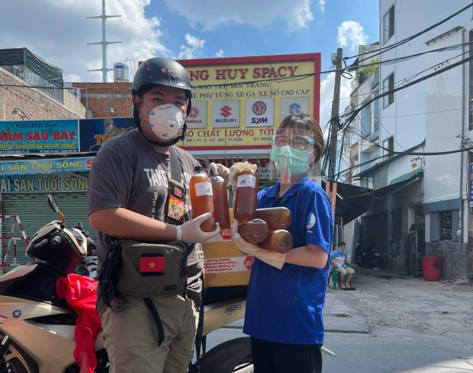 Trung Hiếu tặng trà tắc cho những tình nguyện viên, chiến sĩ trực chốt chặn ở quận Gò Vấp trưa ngày 3/6. Ảnh: Hiếu Nguyễn.