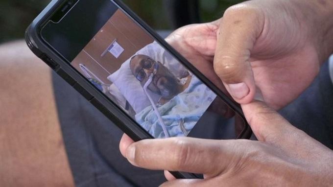Garza xem lại những bức ảnh của chính mình khi đang chiến đấu với Covid-19. Ảnh: ABCNews.