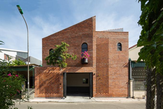 Công trình gây ấn tượng với mặt tiền sử dụng gạch trần. Kiến trúc sư bố trí những ô hở để bớt cảm giác kiên cố và hỗ trợ lưu thông gió.