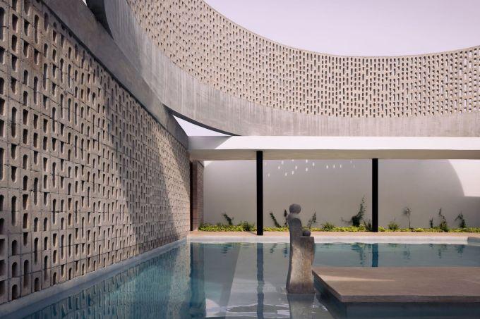 Nhờ những lớp tường bê tông, gia chủ thoải mái thư giãn ở bể bơi mà không sợ nắng.
