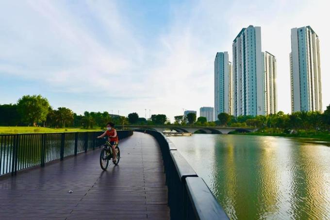 Em bé chạy xe đạp trên cầu gỗ bắc qua hồ Thiên Nga.