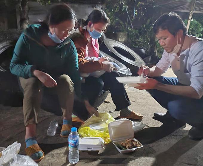 Nhà báo Hoàng Quân và những người Mông hồi hương ăn vội bữa cơm bên đường trên hành trình từ Đà Nẵng ra Nghệ An. Ảnh: Nhân vật cung cấp.