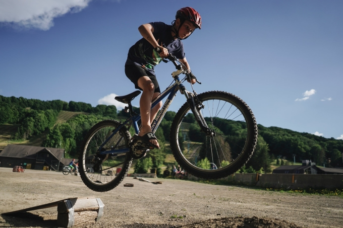 Cậu bé Eli Feuerstein, 9 tuổi đi xe đạp qua các tấm ván và khúc gỗ trong mùa hè 2020. Một số đứa trẻ khác còn tham gia những trò mạo hiểm hơn nữa. Ảnh: Nytimes