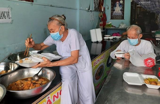 Bà Nguyễn Thị My, 70 tuổi và chồng, ông Trần Văn Hồng, 86 tuổi, đang chuẩn bị cơm chay, phát miễn phí cho người gặp khó khăn, sáng 2/10. Ảnh: Diệp Phan.