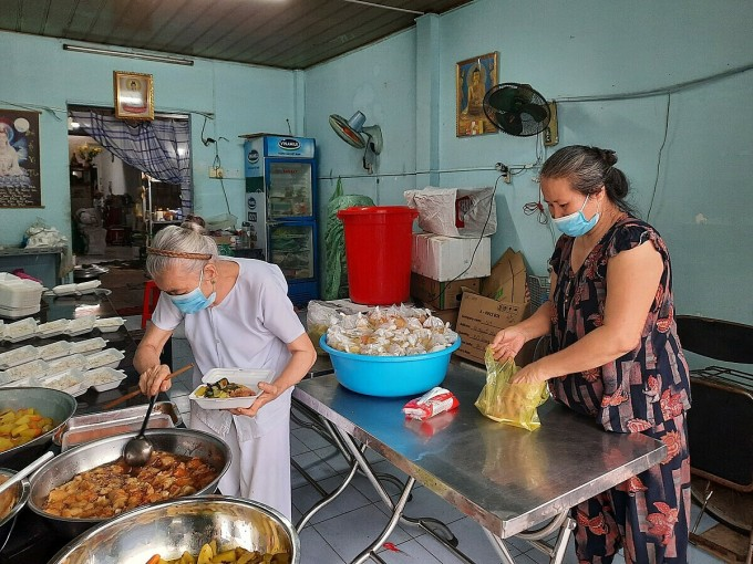 Mấy tháng nay, bà Đẹp, 57 tuổi (áo hoa) vốn làm nghề dọn việc nhà thuê thất nghiệp vì dịch nên đến phụ vợ chồng bà My một tay. Ảnh: Diệp Phan.