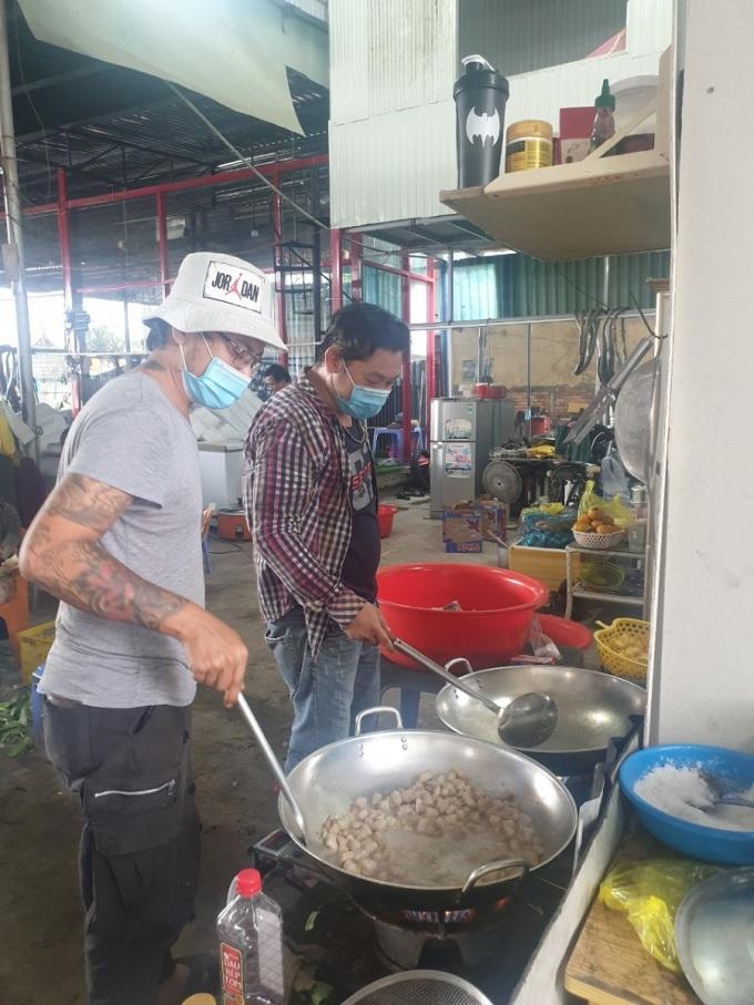 Anh Giang - Tuấn Sport (bên trái)  và bạn nấu cơm 0 đồng tại trong gara sửa xe của mình, cuối tháng 9, tặng những người khó khăn và các chốt kiểm dịch. Ảnh nhân vật cung cấp