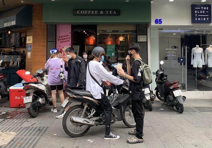 Những người trẻ Sài Gòn ghé mua cà phê tại một cửa hàng ở Mạc Thị Bưởi (Quận 1), trưa 10/10. Ảnh: Trần Tâm.